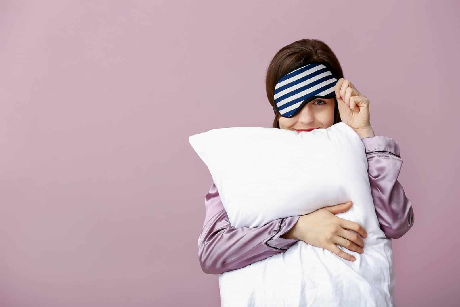 Sleepy woman with mask and pillow on color background